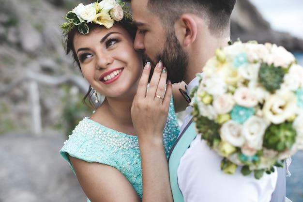 물 근처 산에서 자연에 신부와 신랑. 수트 및 드레스 색상 티파니. 키스하고 포옹합니다. 신부가 웃는다.