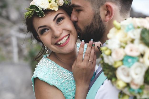 Жених и невеста на природе в горах у воды. костюм и платье цвета тиффани. целовать и обнимать. невеста смеется.