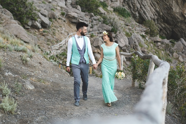 물 근처 산에서 자연에 신부와 신랑. 수트 및 드레스 색상 티파니. 손을 잡고 걸어보세요.