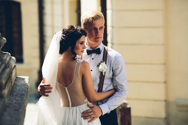 Жених и невеста позируют на старой улице