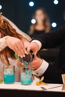 Жених и невеста наливают коктейль