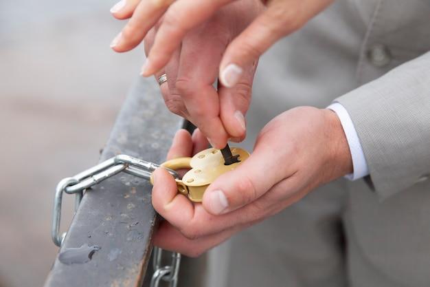 신부와 신랑의 손은 하트 모양의 자물쇠를 닫습니다. 결혼식에서 서명입니다. 고품질 사진