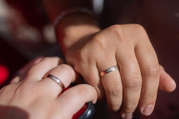 新郎新婦は、結婚式の金の指輪のクローズアップで手と指を示しています。写真、コンセプト。
