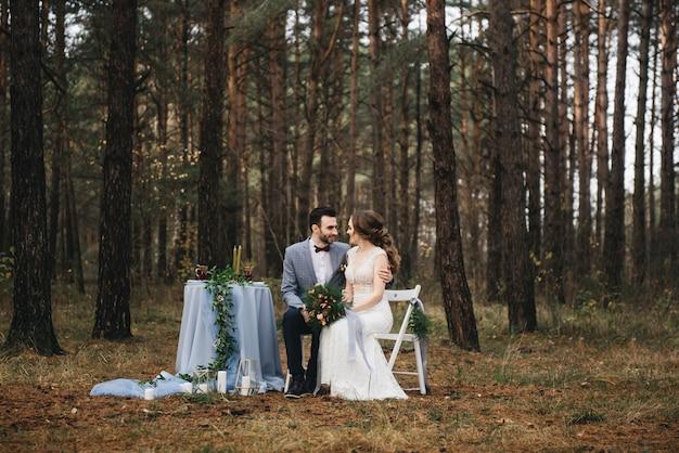 新郎新婦は森の中で2人用のテーブルに座っています