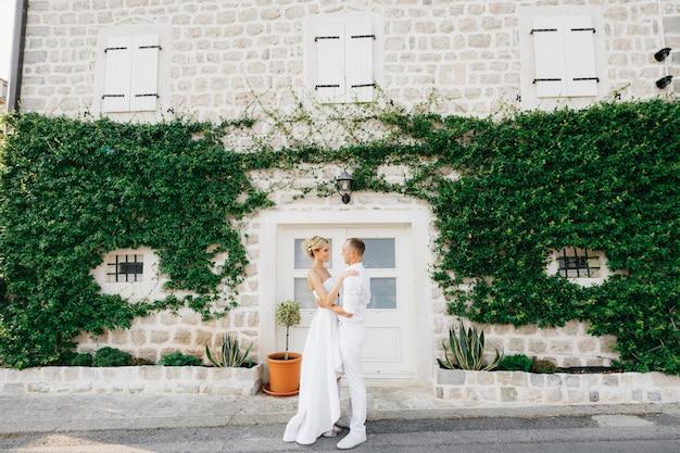 Жених и невеста обнимаются в красивом покрытом плющом белом доме в старом городе пераст.