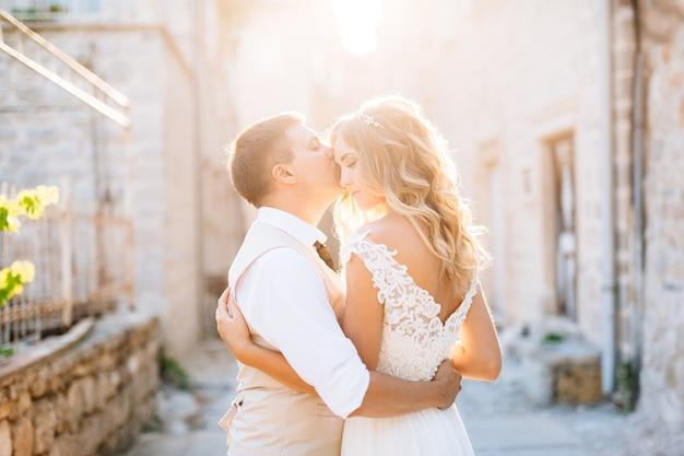 Жених и невеста обнимаются на улицах пераста, жених целует невесту на улице.