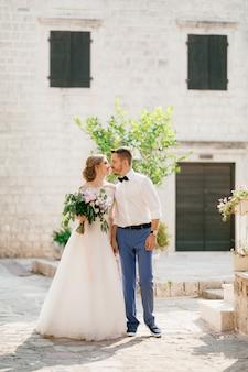 Жених и невеста стоят, держась за руки и целуются возле красивого кирпичного дома в старом городе