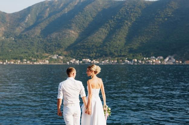 Жених и невеста стоят, держась за руки на берегу которского залива, вид сзади