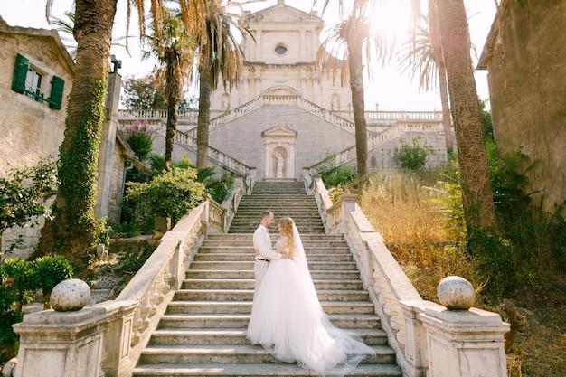 신부와 신랑은 prcanj에있는 축복받은 성모 마리아 교회의 계단에서 포옹하고 손을 잡고 서 있습니다. 고품질 사진