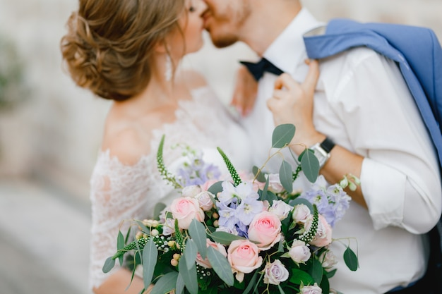 Жених и невеста стоят, обнимаются и целуются возле красивого кирпичного дома