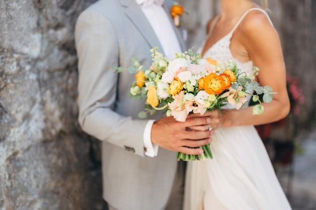 新郎新婦は旧市街のレンガの壁に抱き締めて立って、結婚式の花束を持っています