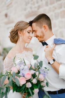 Жених и невеста стоят, обнимая руки возле красивого кирпичного дома в старом городе пераст