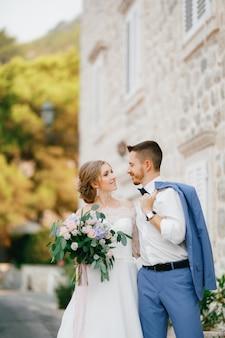 Жених и невеста обнимаются возле красивого кирпичного дома в старом городе пераст