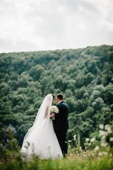 Жених и невеста стоят в поле после свадебной церемонии.