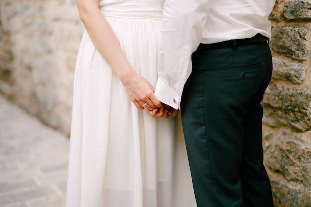 新郎新婦は石の壁の近くに立って、お互いの手をクローズアップに触れて保持します