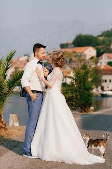 Жених и невеста стоят на пристани, обнимаются и смотрят друг на друга.