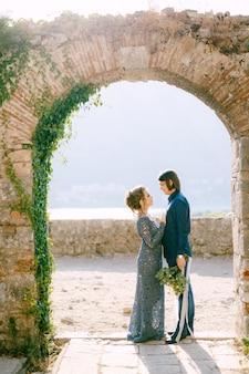 Жених и невеста стоят бок о бок в старинной арке, невеста кладет руки жениху на грудь. фото высокого качества