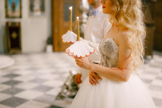 신부와 신랑은 세인트 니콜라스 교회의 제단에서 양초를 손에 들고 서 있습니다.