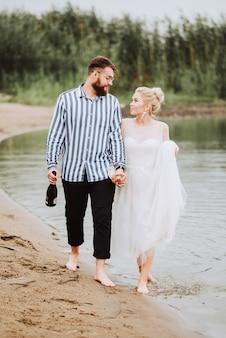 新郎新婦は湖に沿って裸足で散歩し、手をつないでいます。