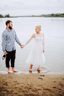 新郎新婦は裸足で川沿いを散歩し、手をつないでいます。