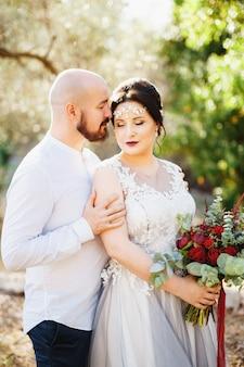 꽃다발을 가진 신부와 신랑은 올리브 과수원 근접 촬영에서 나무 사이 포옹 스탠드