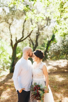 꽃다발을 든 신부와 신랑은 신랑이 키스하는 올리브 과수원의 나무들 사이에서 포옹합니다.