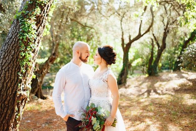 꽃다발을 든 신부와 신랑은 올리브 과수원의 나무들 사이에서 포옹합니다.