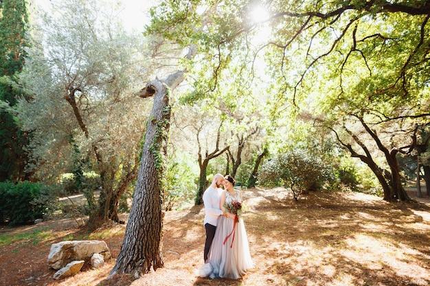 꽃다발을 든 신부와 신랑은 올리브 과수원의 특이한 나무 근처에서 포옹합니다.