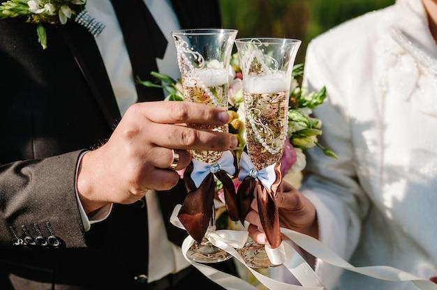 결혼식에 서있는 샴페인 잔을 들고 웨딩 부케와 신부와 신랑