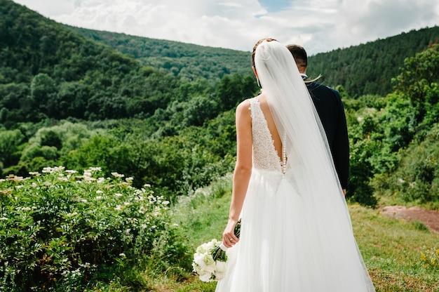 Жених и невеста со свадебным букетом, держась за руки и стоя, глядя на горы. Premium Фотографии