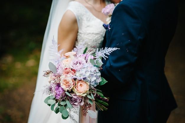 Жених и невеста со свадебным букетом, держась за руки и стоя на свадебной церемонии на открытом воздухе на заднем дворе природы.
