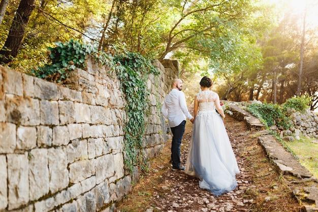 Невеста и стоять, держась за руки возле старой каменной стены среди деревьев в оливковой роще позади