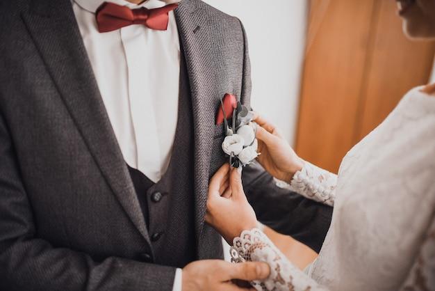Невеста прикрепляет петлицу к будущему мужу любимого жениха в костюме. руки молодоженов крупным планом
