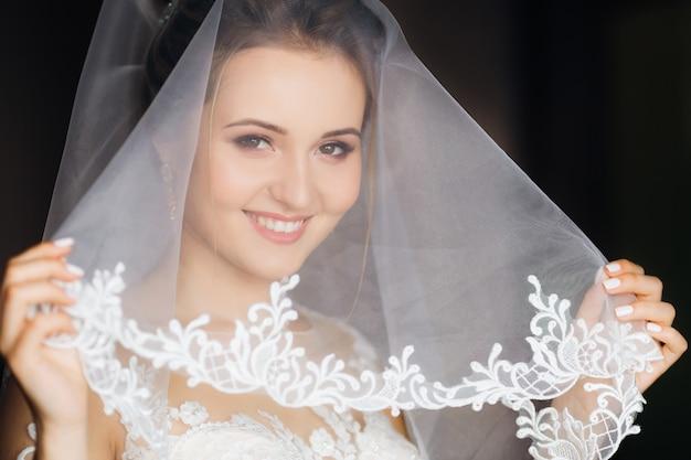花嫁は結婚式のベールで顔を覆い、カメラをのぞき込みます。美しいメイクと笑顔。