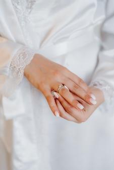 Невеста нежно трогает свое дорогое обручальное кольцо