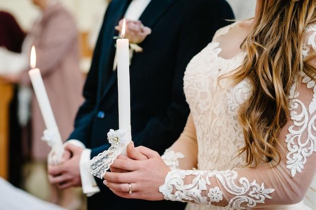Невеста, жених держит в руках свадебную свечу. зажигать свечу. духовная пара, держащая свечи во время свадебной церемонии в христианской церкви. крупным планом.