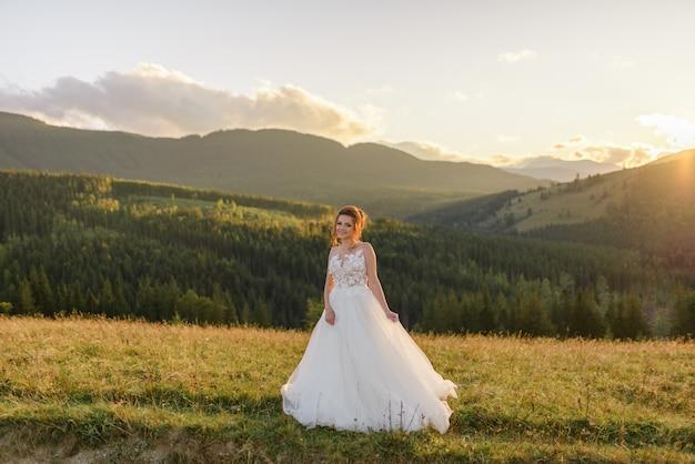 花嫁は日没で山の風景に対してポーズをとります。