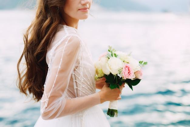 花嫁はバラの花束を手に持って、コトル湾の桟橋にクローズアップで立っています。高品質の写真