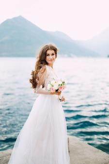 Невеста держит в руках букет роз и стоит на пристани в которской бухте.