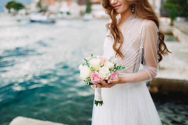 花嫁はバラの花束を手に持ち、ペラストの旧市街近くの桟橋に立っています。