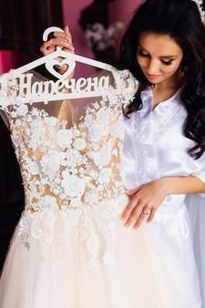 Невеста держит вешалку со свадебным платьем и смотрит на нее.