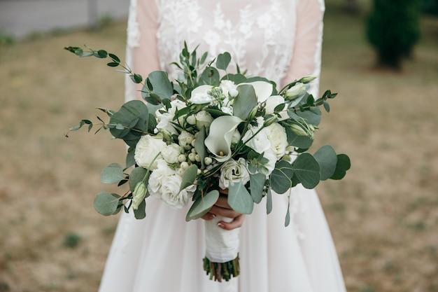 신부는 고급스러운 장미 꽃다발을 손에 들고 있습니다.
