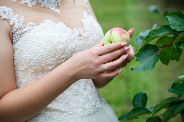 花嫁は熟した赤いリンゴを手に持っています