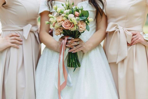 花嫁は彼女の手でウェディングブーケを持っています
