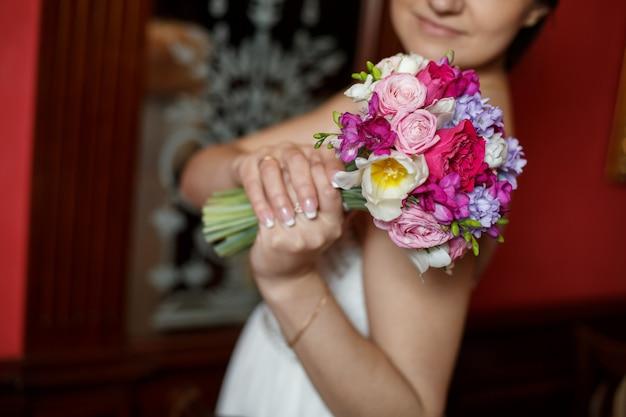 Невеста держит свадебный букет из красных и розовых цветов в помещении. молодая девушка в белом платье с нежным праздничным букетом роз в руках. стильная цветочная композиция из ярких цветов крупным планом