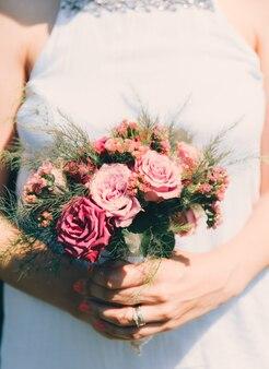 花嫁は彼女の手でバラのウェディングブーケをクローズアップ