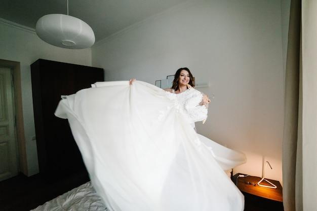Невеста держит в руках свадебное платье и крутится вместе с ней на кровати. стильное винтажное элегантное платье с кружевом. подготовка к свадьбе утром.