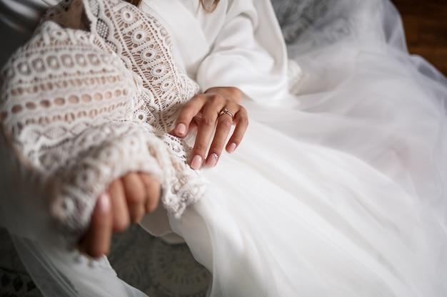 신부는 결혼식 날 흰 드레스를 손에 들고 있습니다.