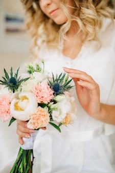 花嫁は手に持って、牡丹、バラ、トルコギキョウと花束に優しく触れます。