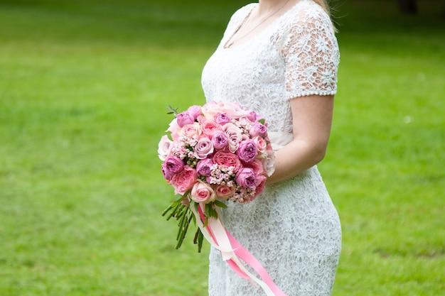 花嫁は結婚式のアクセサリーを手に持っています-バラで作られた花束